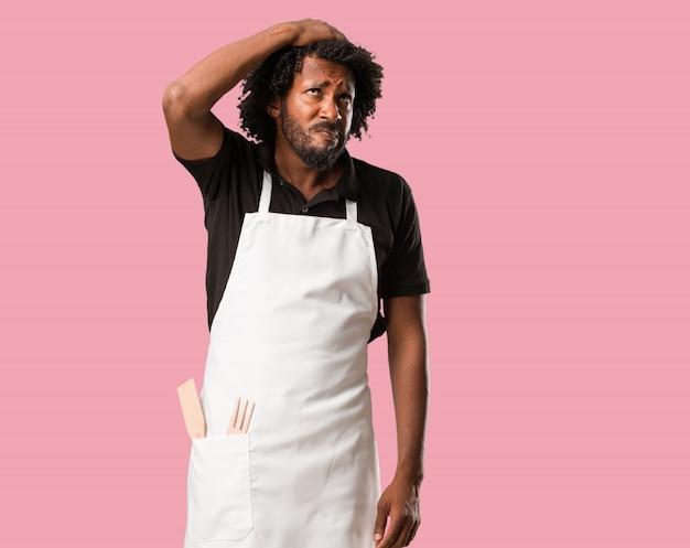 Hübscher afroamerikanerbäcker besorgt und überwältigt, vergesslich, verwirklichen etwas