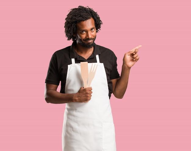 Hübscher afroamerikanerbäcker, der auf die seite, lächelndes überraschtes darstellen etwas zeigt, natürlich und beiläufig