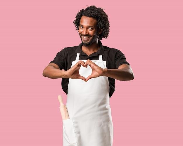 Hübscher afroamerikanerbäcker, der ein herz mit den händen macht