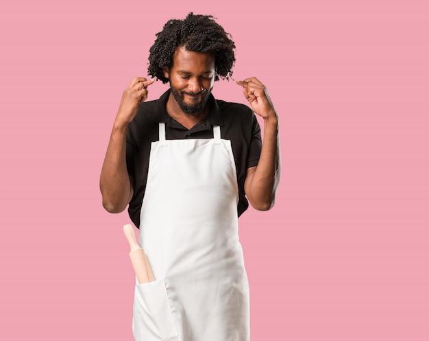 Hübscher afroamerikanerbäcker, der seine finger kreuzt, wünscht, für zukünftiges projec glücklich zu sein