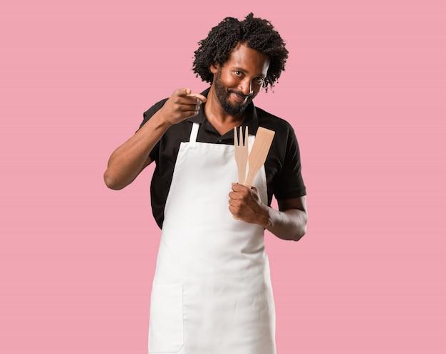 Hübscher afroamerikanerbäcker nett und lächeln, zeigend auf die front