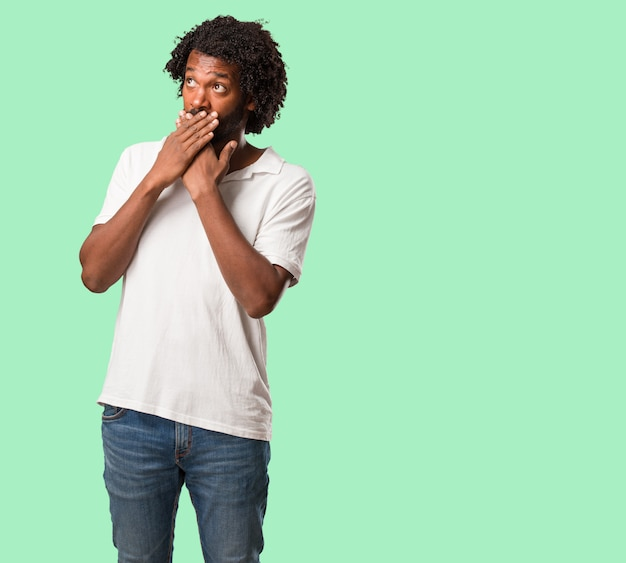 Hübscher afroamerikanerbedeckungsmund, symbol der ruhe und der unterdrückung, versuchend, nichts zu sagen
