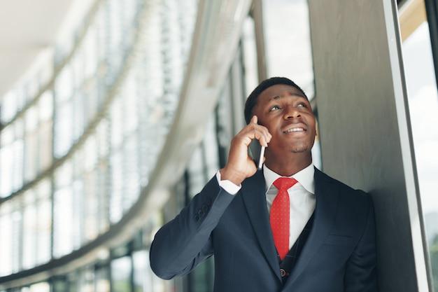Hübscher afroamerikanergeschäftsmann, der am handy im modernen büro spricht