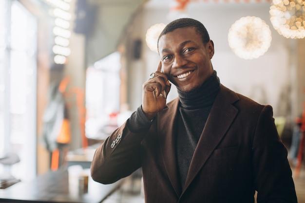 Hübscher afroamerikanergeschäftsmann, der auf smartphone im café spricht.