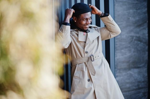 Hübscher afroamerikanermann, der draußen im schwarzen hut und im beigen mantel aufwirft.