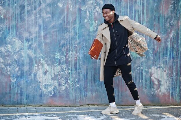 Hübscher afroamerikanermann, der draußen im schwarzen hut und im beigen mantel mit ordner in der hand aufwirft.