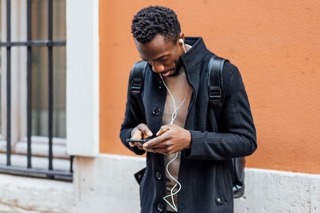 Hübscher afroamerikanermann, der handy verwendet.