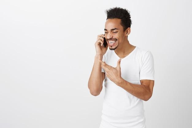Hübscher afroamerikanermann, der lebhaft auf handy spricht und gestikuliert, während er etwas erklärt