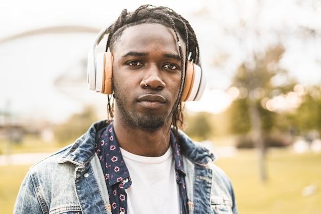 Hübscher afroamerikanermann des porträts und glücklicher junger mann mit musikkopfhörerstraße