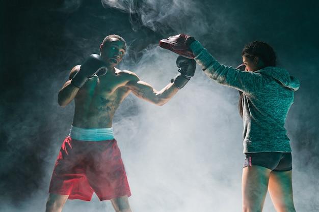Hübscher afroamerikanischer boxer mit nacktem oberkörper übt schläge mit einem partner im kampfclub