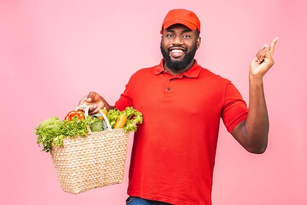 Hübscher afroamerikanischer lieferbote, der paketbox des lebensmittelladens vom laden trägt