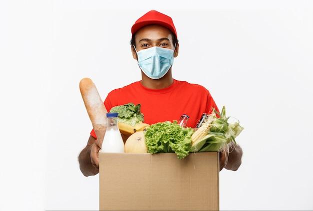Hübscher afroamerikanischer lieferbote, der paketbox des lebensmittellebensmittels und des getränks vom laden trägt.