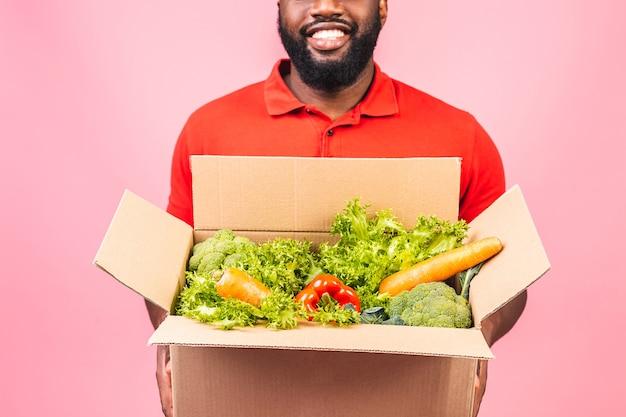 Hübscher afroamerikanischer lieferbote, der paketbox trägt