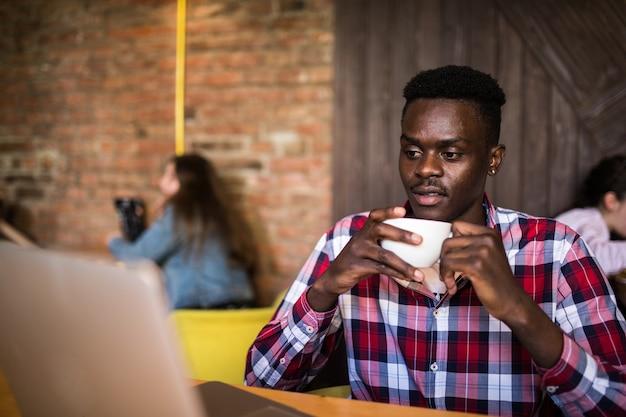 Hübscher afroamerikanischer mann in der freizeitkleidung, die eine tasse kaffee hält und laptop verwendet.