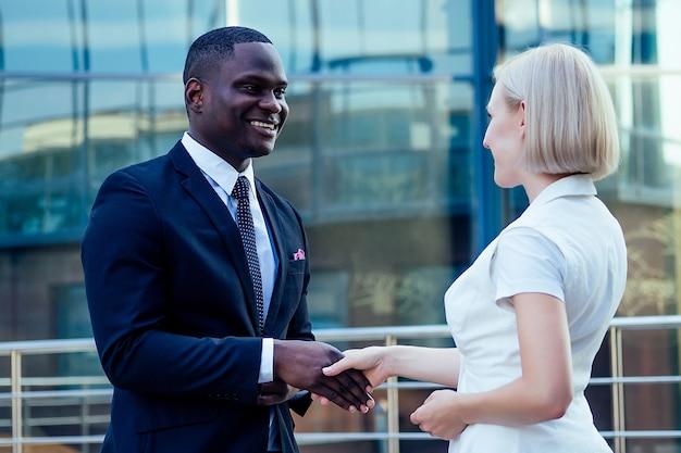 Hübscher afroamerikanischer mann in einem schwarzen anzug, der hand mit einem geschäftsfrau-partnerstadtbildglasbürohintergrund schüttelt. teamwork und erfolgreiche deal-idee