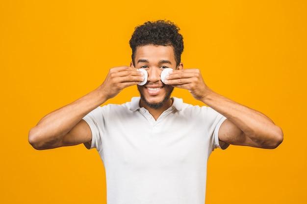 Hübscher afroamerikanischer schwarzer mann, der gesichtshaut mit wattepads reinigt