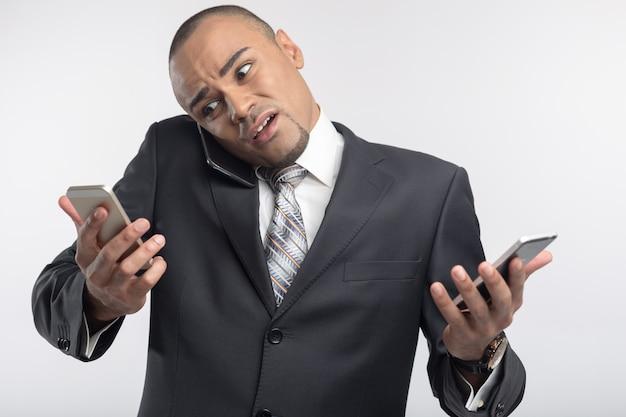 Hübscher afrogeschäftsmann unter verwendung seines smartphoneporträts
