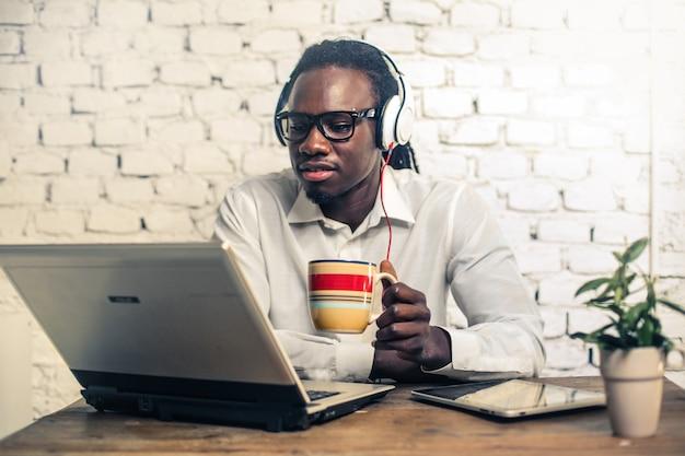 Hübscher afromann, der an einem laptop arbeitet