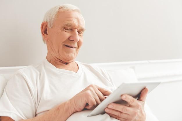 Hübscher alter mann benutzt eine digitale tablette und ein lächeln