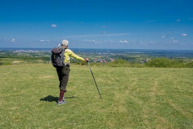 Hübscher alter mann, der auf einer wiese am berghang wandert