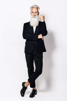 Hübscher alter mann, der stilvollen schwarzen anzug auf weiß trägt