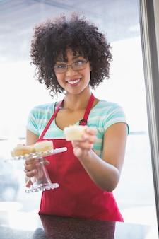 Hübscher angestellter, der kleinen kuchen lächelt und anbietet