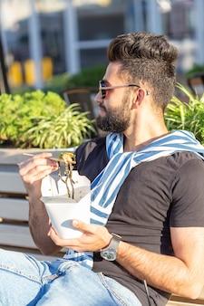 Hübscher arabischer junger hipster-typ, der chinesische nudeln mit holzstäbchen isst, die an einem warmen sommertag in einem park draußen sitzen. das konzept der ruhe und des naschens auf der straße.