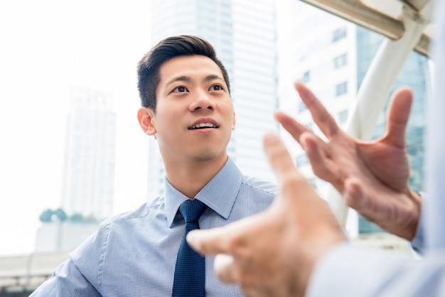 Hübscher asiatischer chinesischer geschäftsmann, der draußen mit partner spricht