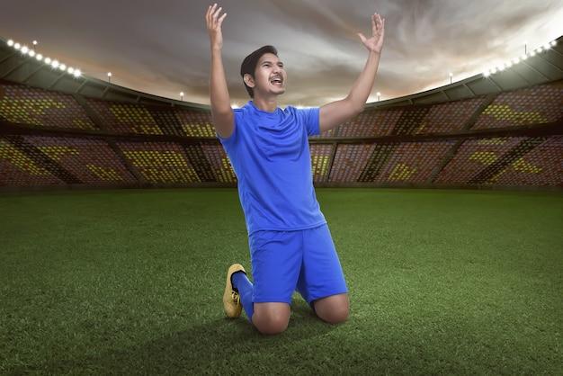 Hübscher asiatischer fußballspieler glücklich für das gewinnen des matches