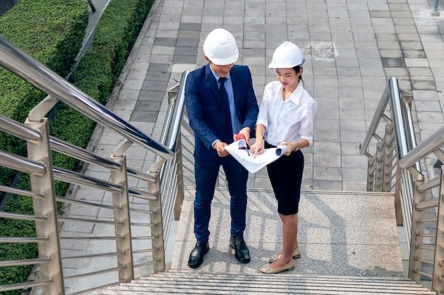 Hübscher asiatischer geschäftsingenieur der managerin, die lächelt und über erfolgsarbeit mit partnern spricht.