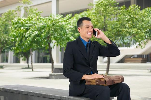 Hübscher asiatischer geschäftsmann, der an seinem handy spricht