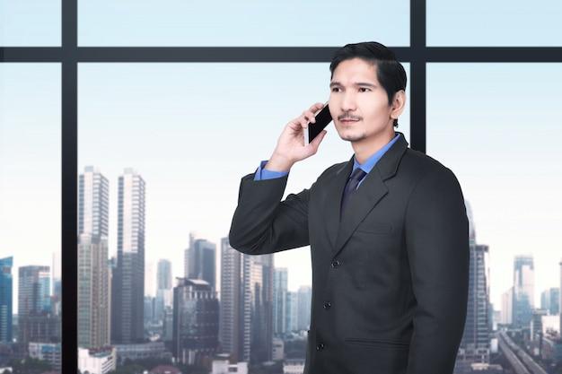 Hübscher asiatischer geschäftsmann, der auf dem mobiltelefon spricht