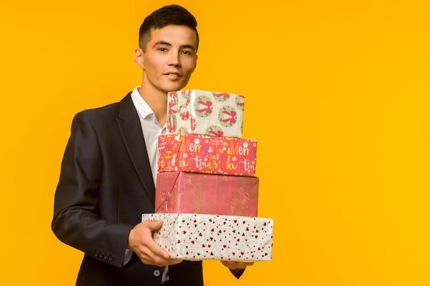 Hübscher asiatischer geschäftsmann, der geschenkbox hält