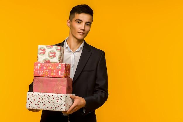 Hübscher asiatischer geschäftsmann, der geschenkbox über gelbem hintergrund - bild hält
