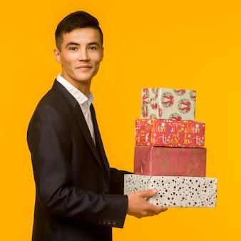 Hübscher asiatischer geschäftsmann, der geschenkbox über gelbem hintergrund hält