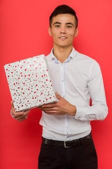 Hübscher asiatischer geschäftsmann, der geschenkbox über rotem hintergrund - bild hält
