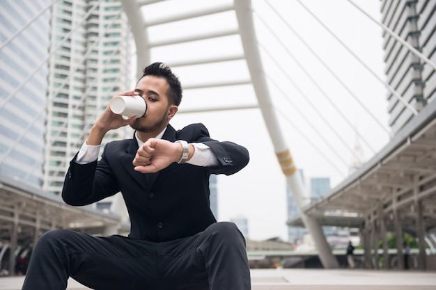 Hübscher asiatischer geschäftsmann, der heißen kaffee trinkt und armbanduhr betrachtet, um zeit zu überprüfen