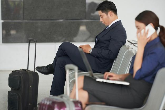 Hübscher asiatischer geschäftsmann, der in flughafen wartet