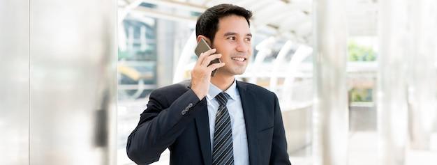 Hübscher asiatischer geschäftsmann, der um smartphone beim gehen in die stadt ersucht