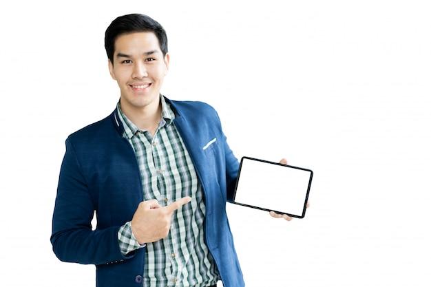 Hübscher asiatischer geschäftsmann im gesellschaftsanzug, der die moderne tablette mit leerem weißem schirmabschluß hochhält.