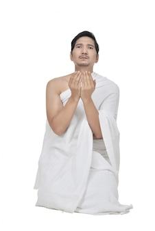 Hübscher asiatischer hadsch-pilger, der zum gott betet