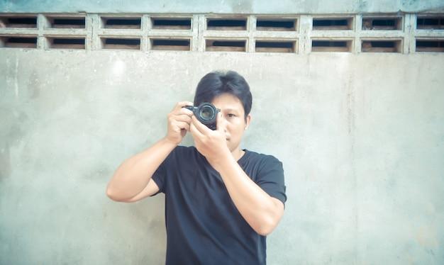Hübscher asiatischer kerl, der foto mit kamera macht