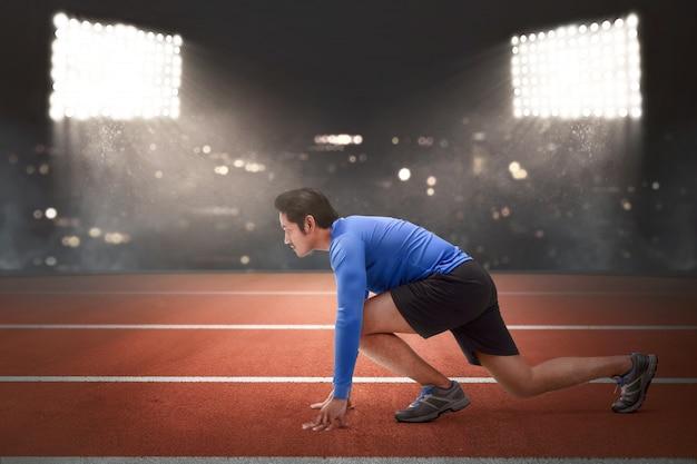 Hübscher asiatischer läufermann in der bereiten position zu laufen