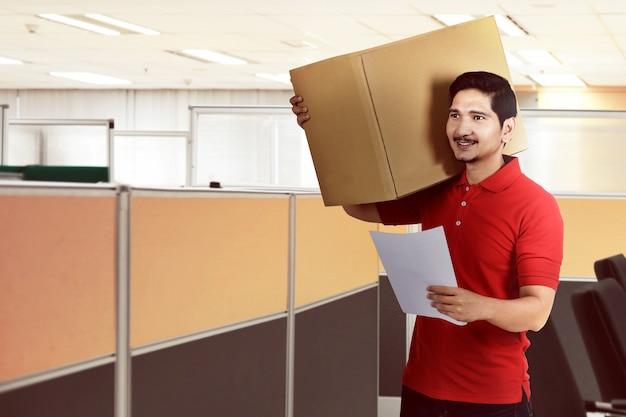 Hübscher asiatischer lieferbote, der das paket hält