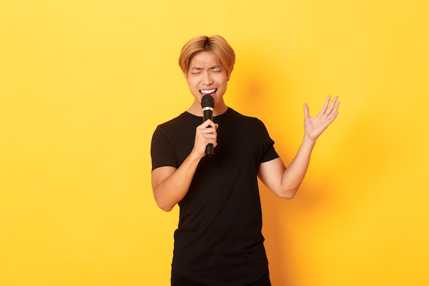 Hübscher asiatischer männlicher sänger, koreanischer typ, der lied bei karaoke im mikrofon mit leidenschaft singt, über gelber wand stehend