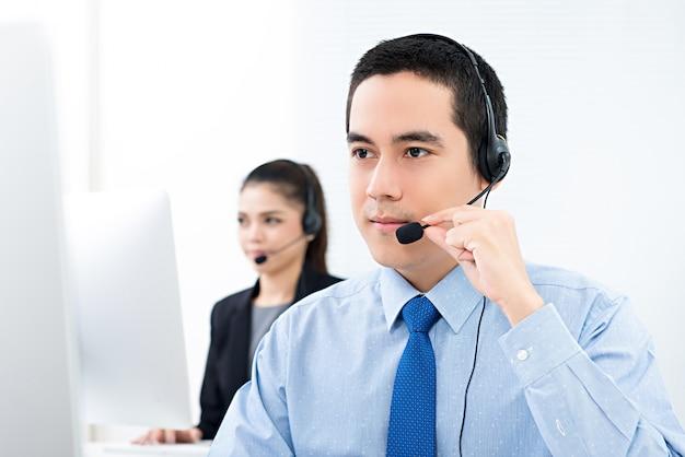 Hübscher asiatischer männlicher telemarketing-kundendienstmitarbeiter, der in call-center arbeitet