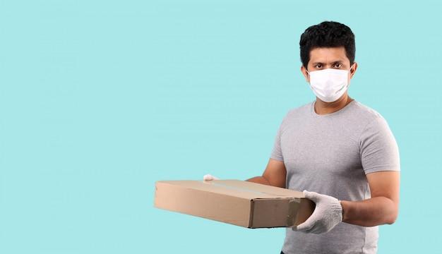 Hübscher asiatischer mann, der gesichtsmaske trägt, um vor keimen und viren zu schützen. halten mit paketpostfach in pappkartons auf hellblauem hintergrund im studio.