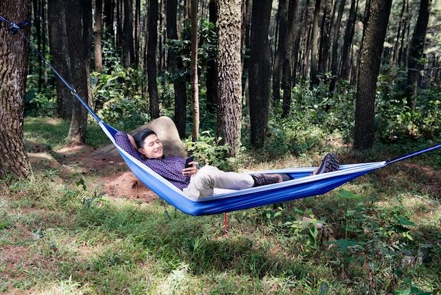 Hübscher asiatischer mann, der handy bei der entspannung auf der hängematte verwendet