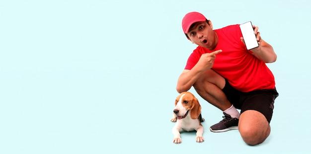 Hübscher asiatischer mann in der roten kappe und im beagle-hund