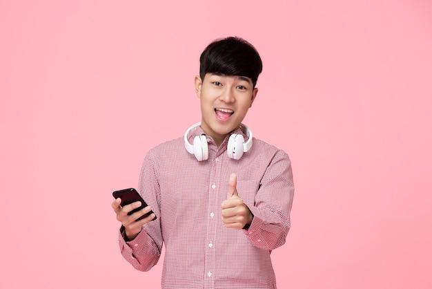 Hübscher asiatischer mann mit den kopfhörern und smartphone, die daumen aufgeben
